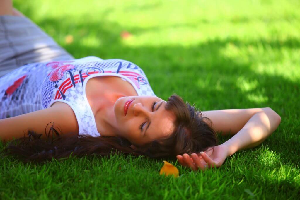 芝生の上で寝転んでいる女性