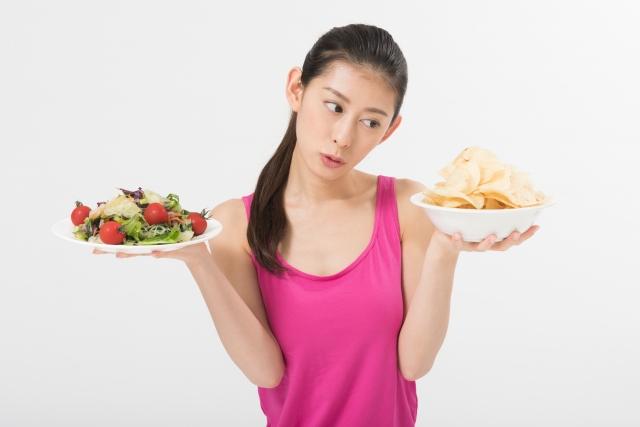 サラダとスナックどちらを食べようか迷う女性
