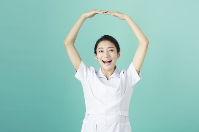 丸を手で作っている女性