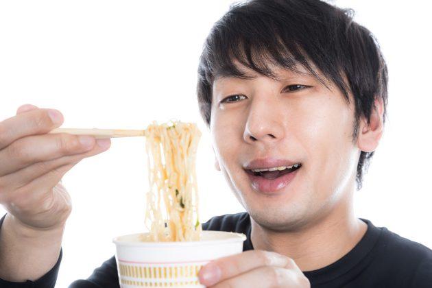 幸せそうな顔でカップラーメンを食べる男性
