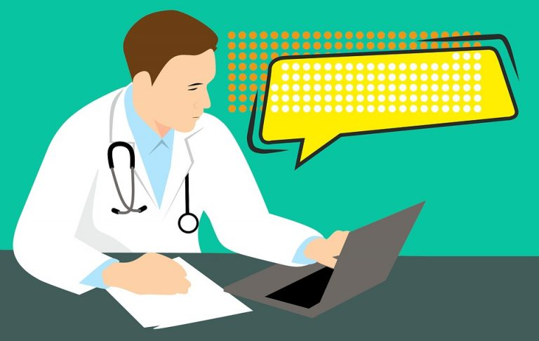 パソコンを見ながら診断書を書くドクター
