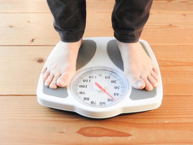 ダイエットしたくて体重計に乗る女性