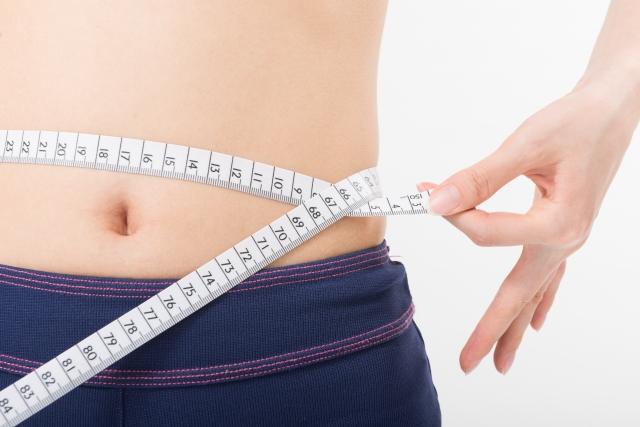 腰にメジャーを巻いてダイエットの成果を見る女性