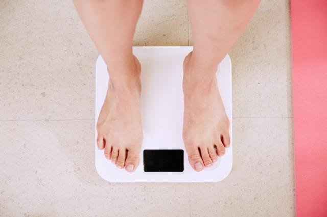 サラダチキンダイエット1週間の効果を知るために体重計に乗る女性