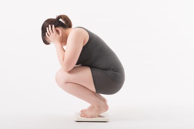 体重計に乗り頭を抱える女性