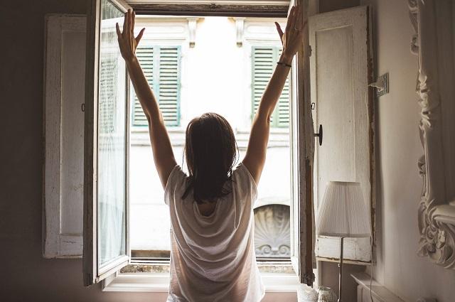 窓を開けて両手を広げる女性