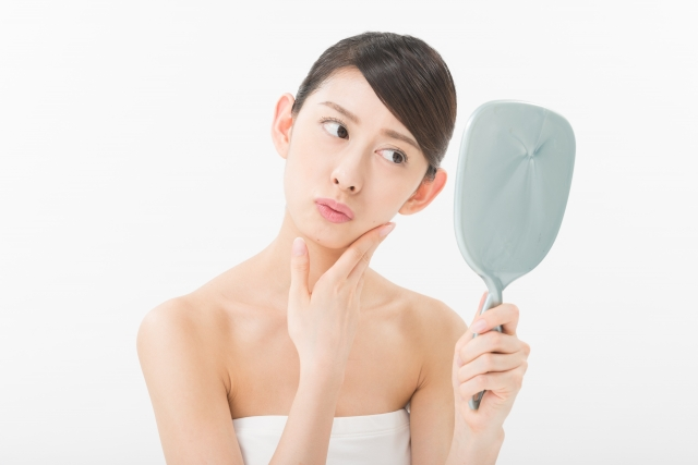 鏡で顔を確認する女性